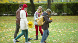 Two kids and their parents walking in autumn park Footage