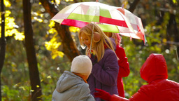 Twin brothers and sisters enjoying sun shower in the autumn park Footage