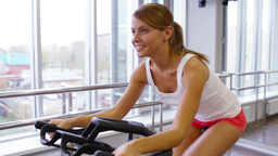 Smiling sportswoman building her leg muscles riding a fitness machine Footage