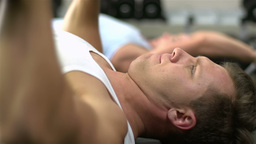 Close-up of a muscular bodybuilder lifting dumbbells in lying position Footage