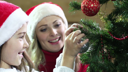 Close-up of a little cutie hanging a sparkling bauble on a Christmas tree togeth Footage