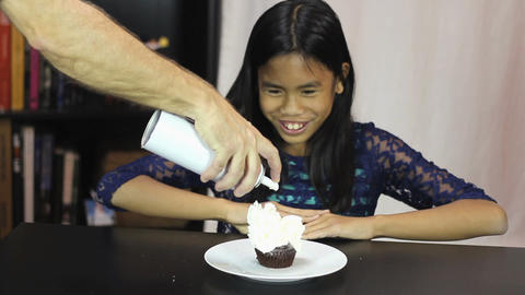 Asian Girl Enjoys Whip Cream On Birthday Cupcake stock footage