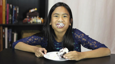 Cute Asian Girl Eating Birthday Cupcake Footage