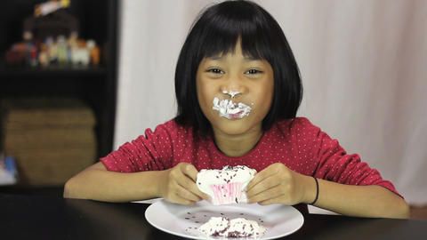 Little Asian Girl Eating Yummy Chocolate Cupcake stock footage