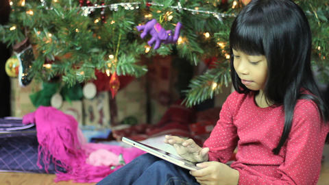 Seven Year Old Asian Girl Uses Tablet By Christmas Footage
