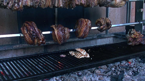 rotisserie of meat cooking on fire Footage