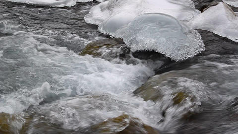 Transparent pure water flows among ice and rock Footage