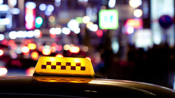 Timelapse of city traffic at night behind taxi sig Footage