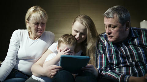 Family watching boy playing game on touchpad Footage
