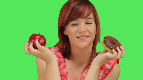 Woman deciding between Doughnut and Apple Footage