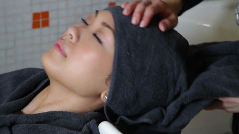 Woman drying hair from client in hair salon Footage