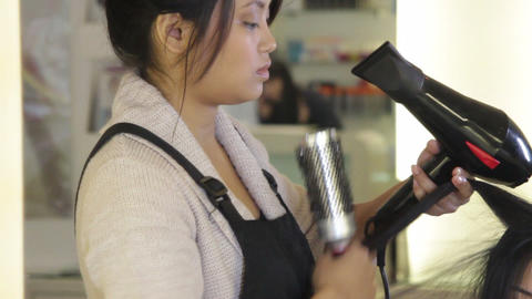 Hairdresser drying and brushing hair of female in hair salon Footage