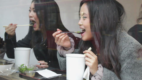 Asian female friends eating noodles Footage