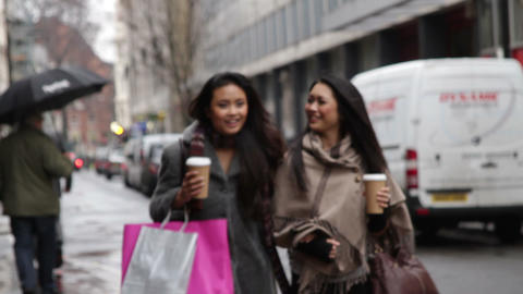 Female walking in shopping street with coffee Live Action