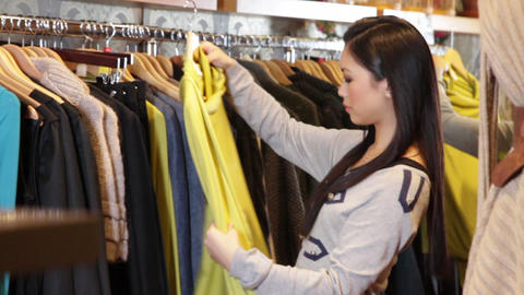Female looking in clothes shop at dresses Live Action
