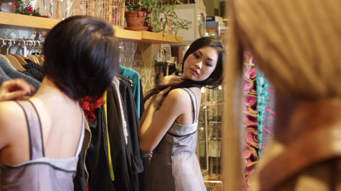 Female in clothes shop fitting on dress and looking in mirror Live Action
