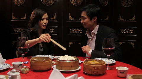 Female feeding male with dumplings in Chinese restaurant Footage