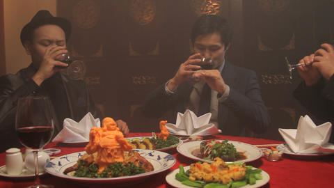 Businessmen toasting wineglasses in Chinese restaurant Footage