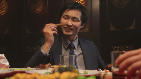 Businessmen toasting glasses and smoking cigars in Chinese restaurant Footage