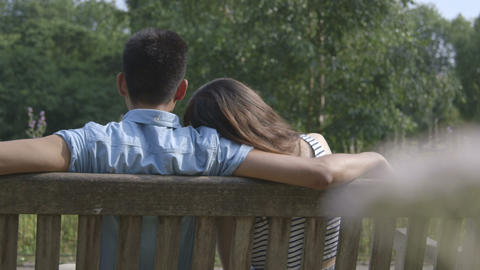 Young Couple Sitting In Park stock footage