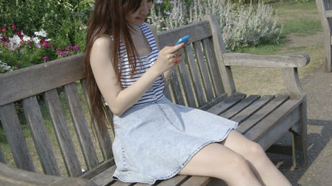 Young woman sitting on bench using mobile phone in park Footage