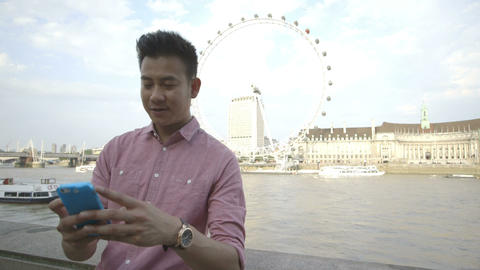 Young man taking self-portrait with big wheel and passenger craft in background Footage