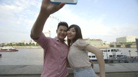 Young couple taking self-portrait with big wheel and passenger craft in backgrou Footage