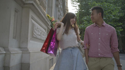 Young couple walking on pavement with shopping bags Footage
