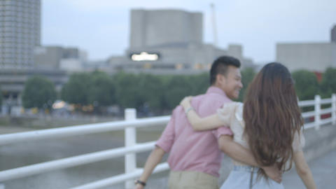 Young couple holding and walking across bridge Footage