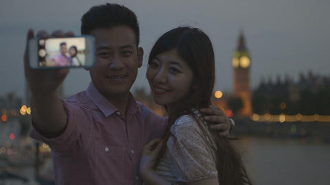 Young couple taking self-portrait with big ben in background Footage