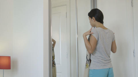Young woman trying clothes near mirror Footage