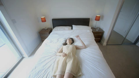Young woman jumps backwards onto bed Footage