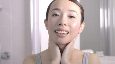 Young woman massaging her face and smiling Footage