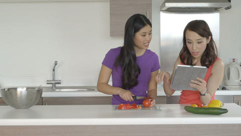 Young women preparing food with help of digital tablet in kitchen Footage