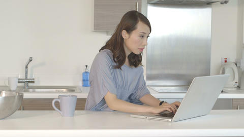 Young woman drinking coffee and working on laptop in kitchen Footage