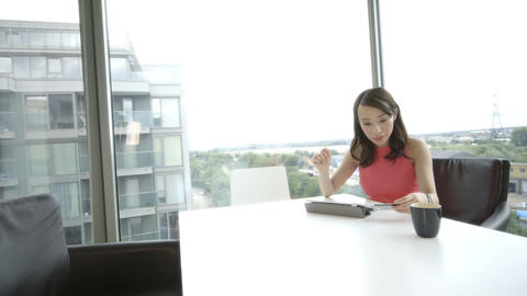 Young woman holding credit card and using digital tablet in office Footage