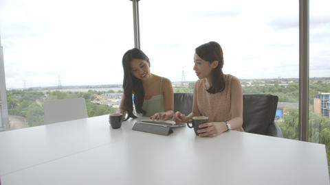 Young women discussing while using digital tablet in office Footage