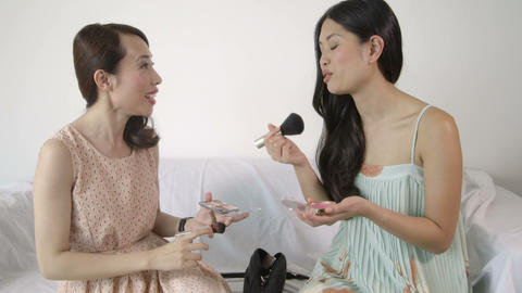 Young woman applying make-up and talking with friend Footage