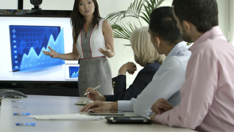 Businesswoman explaining with the help of graph in board room Footage