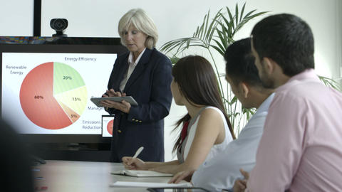Businesswoman explaining with the help of pie chart and tablet in board room Footage