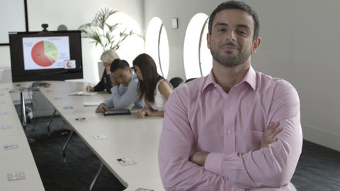 Man sitting with arms crossed while people working in background Footage