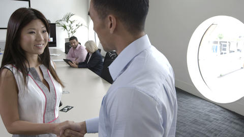 Mans and woman shaking hands in conference room Footage