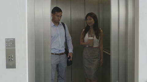 Man and woman holding a disposable cup in lift Footage
