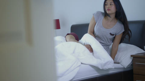 Young woman sitting on bed with man sleeping in background Footage