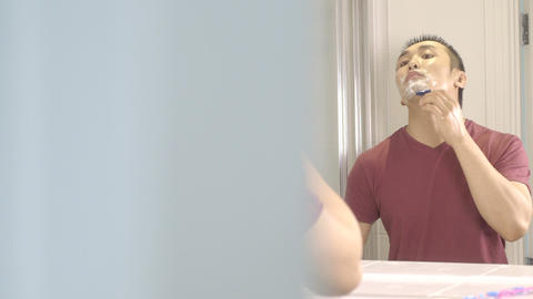 Young man shaving face in bathroom mirror Live Action
