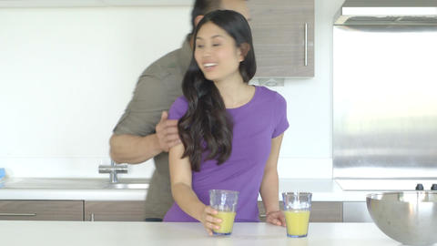 Young couple standing and drinking juice in kitchen Footage