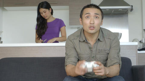 Young couple in kitchen man playing game and woman preparing food Footage
