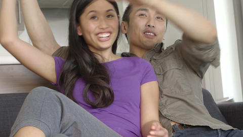 Young couple sitting on sofa and watching TV Footage