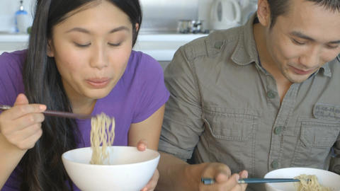 Young couple sitting on sofa and eating noodles Footage