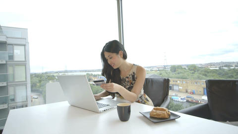 Young woman sitting in office and using laptop Footage